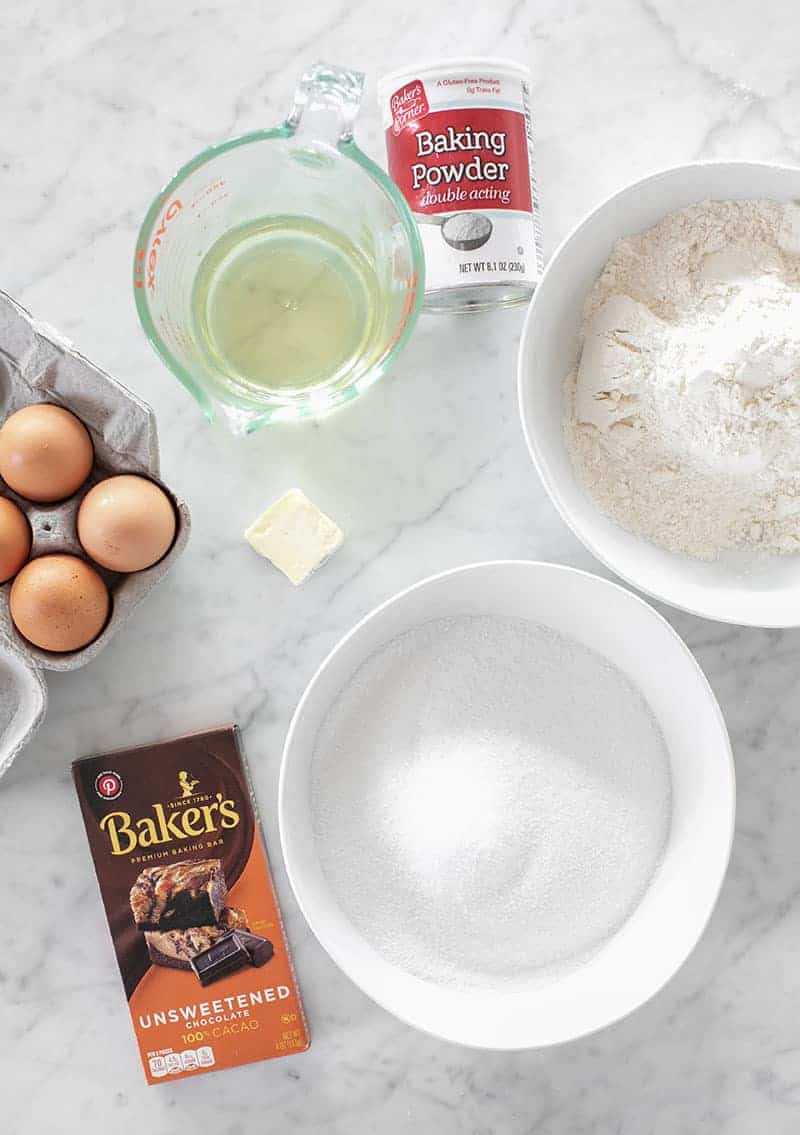 Ingredients to make homemade chocolate brownies. Oil, sugar, flour butter, eggs, chocolate and baking powder.