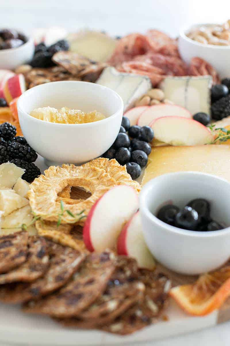Cheese platter with mini white bowls and dried fruit.