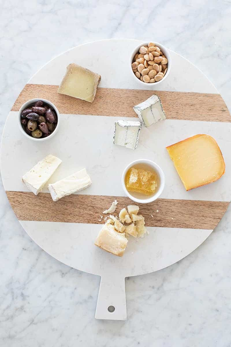 Cheese, honey and olives on a cheese platter.