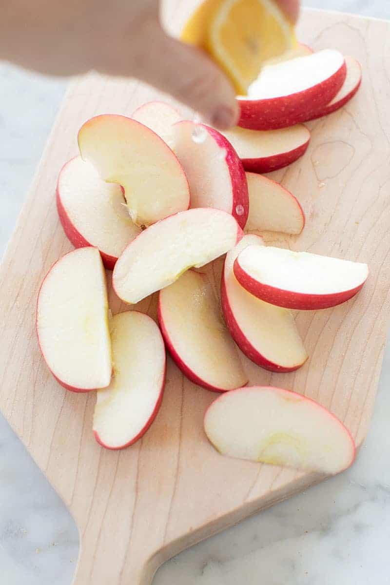 Squeezing fresh lemon over sliced apples.