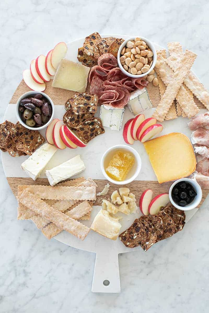 Adding sliced fruit to a cheese board with honey and crackers and meat.