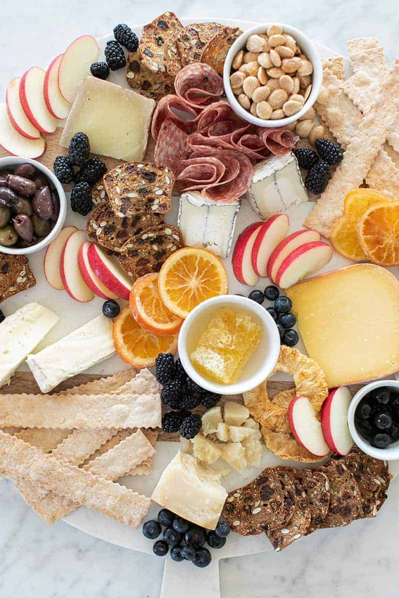 Assembling a cheese board with crackers, cheese, fruit, honey and berries.