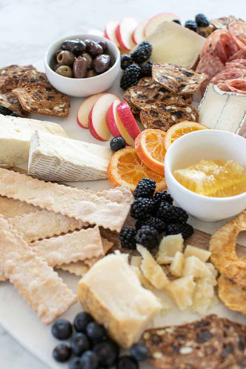 Crackers, berries, cheese, honey, dried fruit on a board.