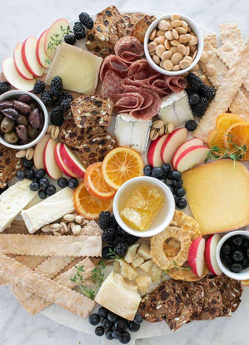 Cheese platter with meat, fruit, honey, cheese, almonds, crackers and dried fruit on a large platter.