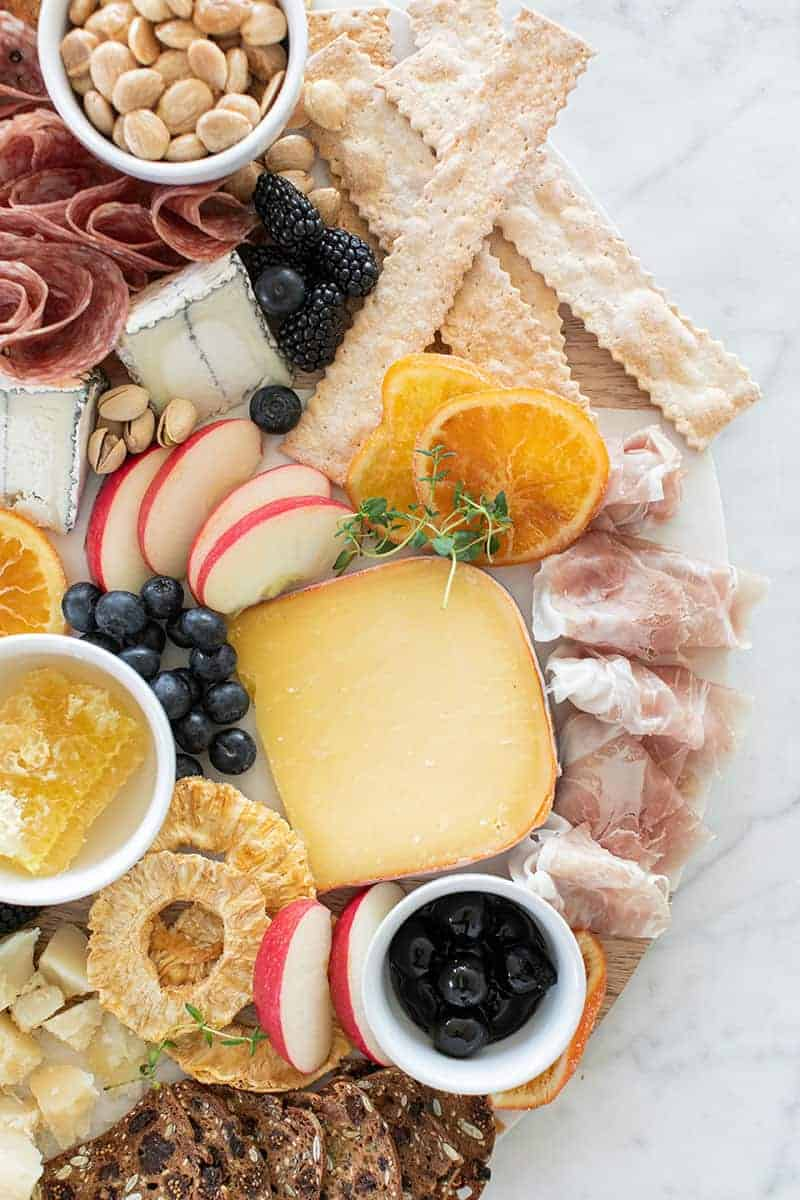 a pretty cheese platter with cheese, meat, berries, crackers and honey.