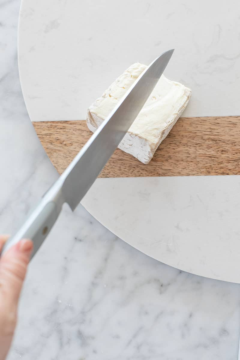 Cutting soft cheese on a cheese board