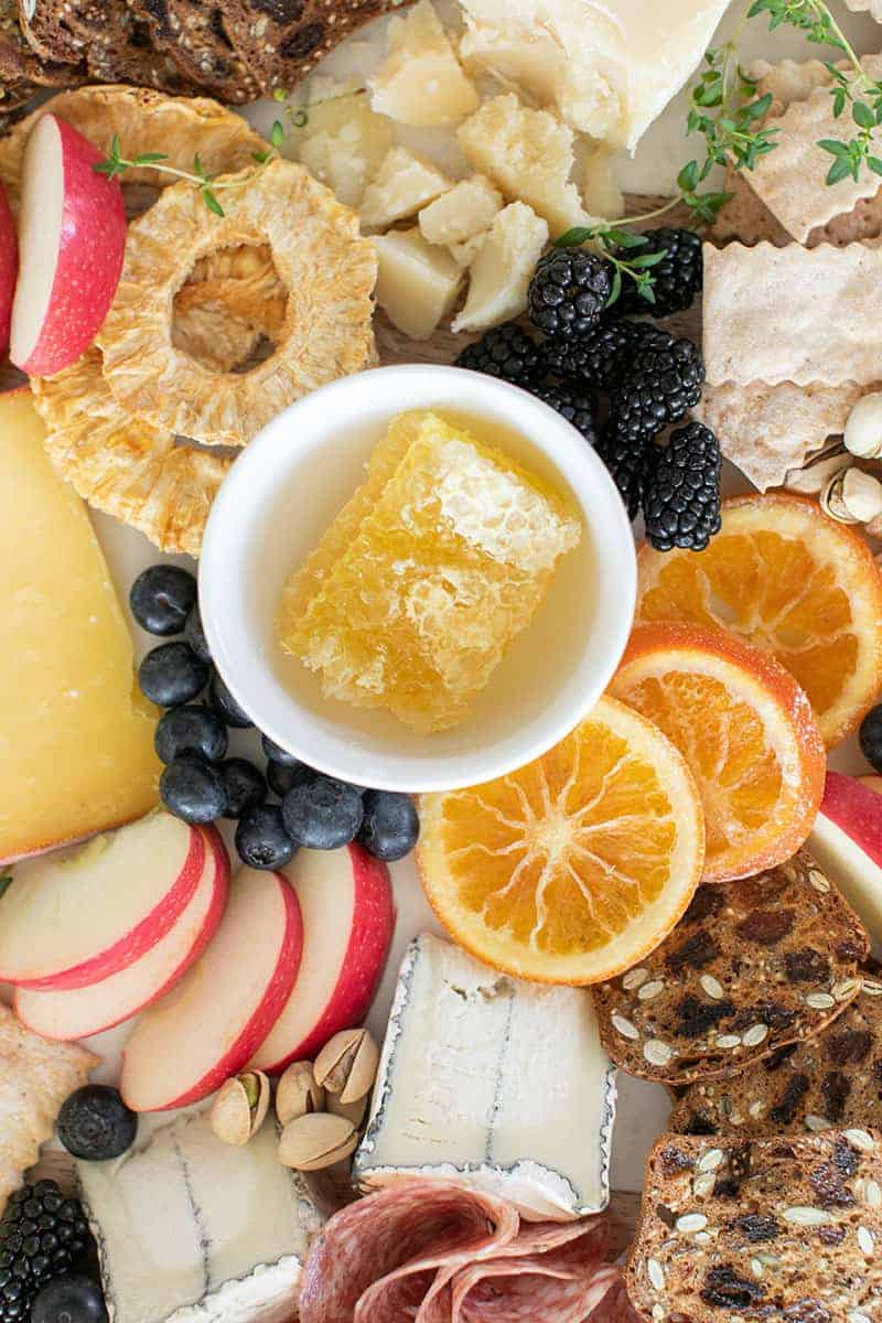 honeycomb on a cheese plate surrounded by fruit, cheese and crackers.