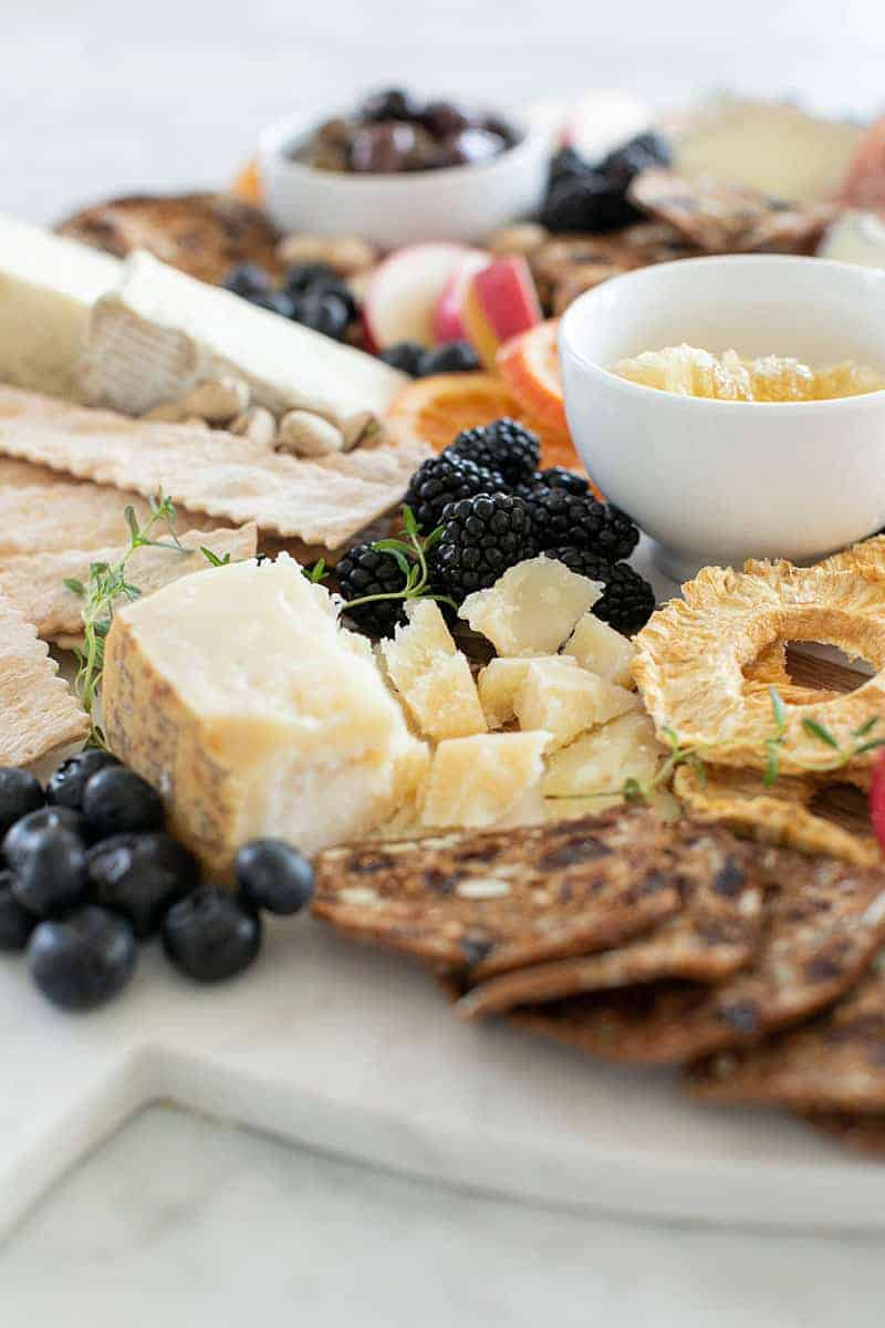 Parmesan cheese in chunks with berries and crackers and dried fruit