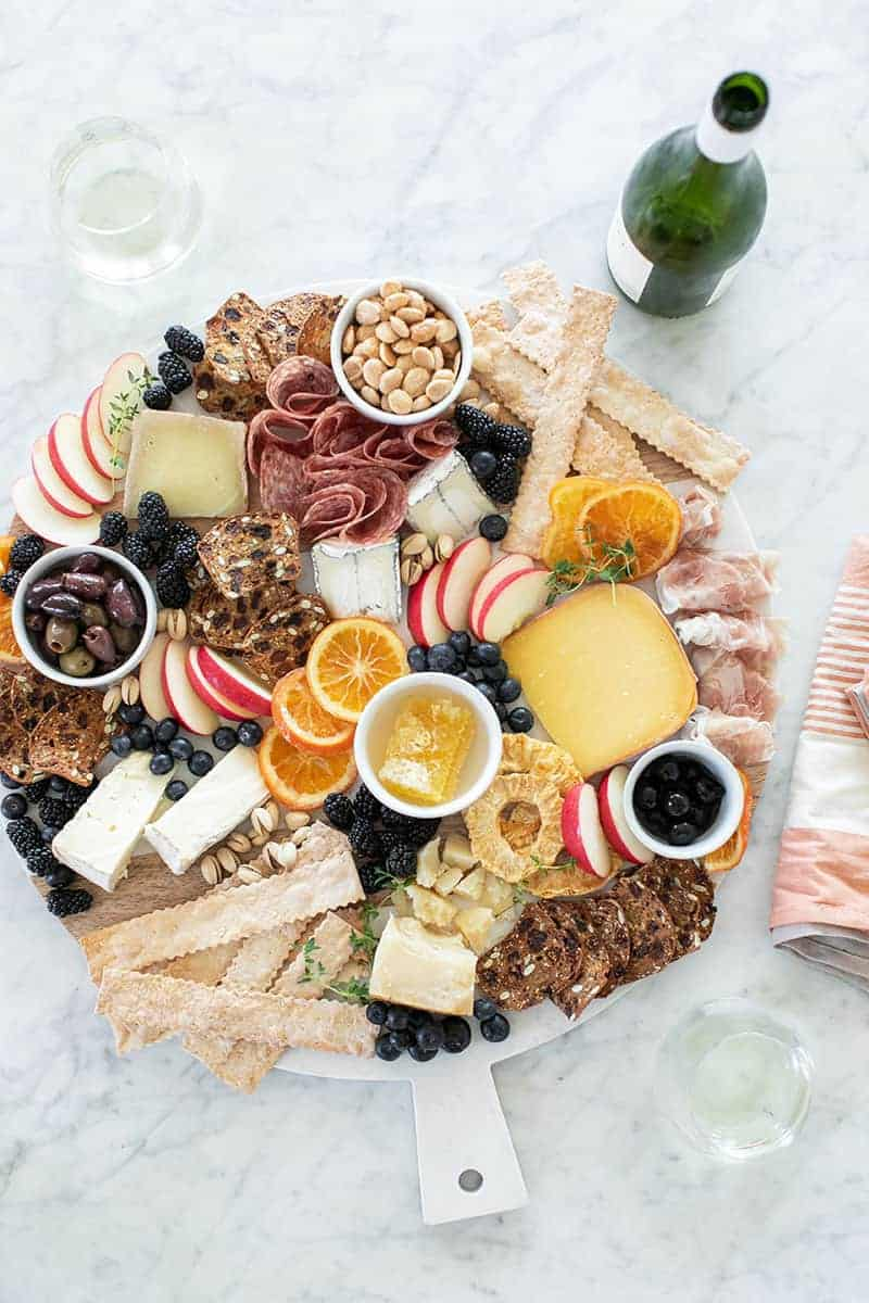 Large cheese board filled with cheese, fruit and charcuterie