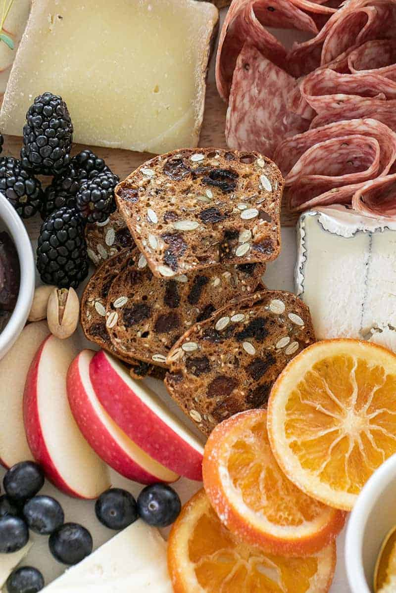 Cracker crips, cheese, sliced apples, blackberries and dried orange slices on a cheese board.