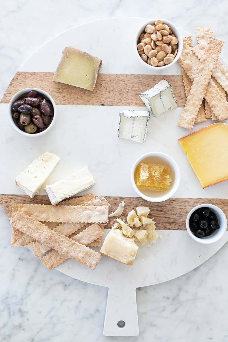adding crackers to a cheese platter