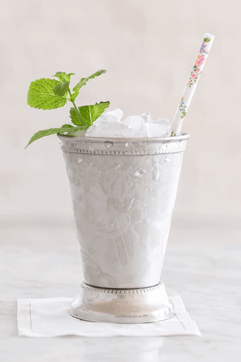 A classic mint julep with floral straw and mint.