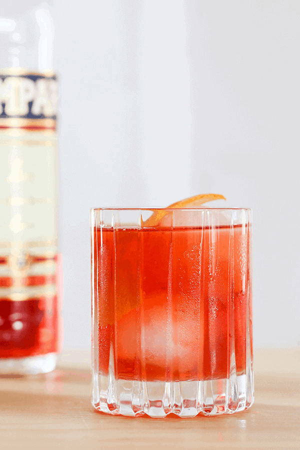A classic Negroni cocktail wit round ice cube and orange rind.