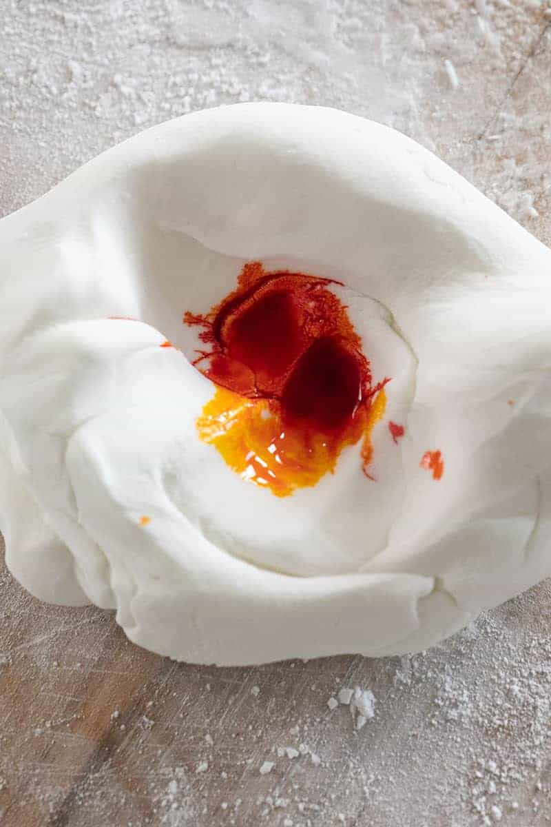 Orange food coloring in white fondant before mixing.