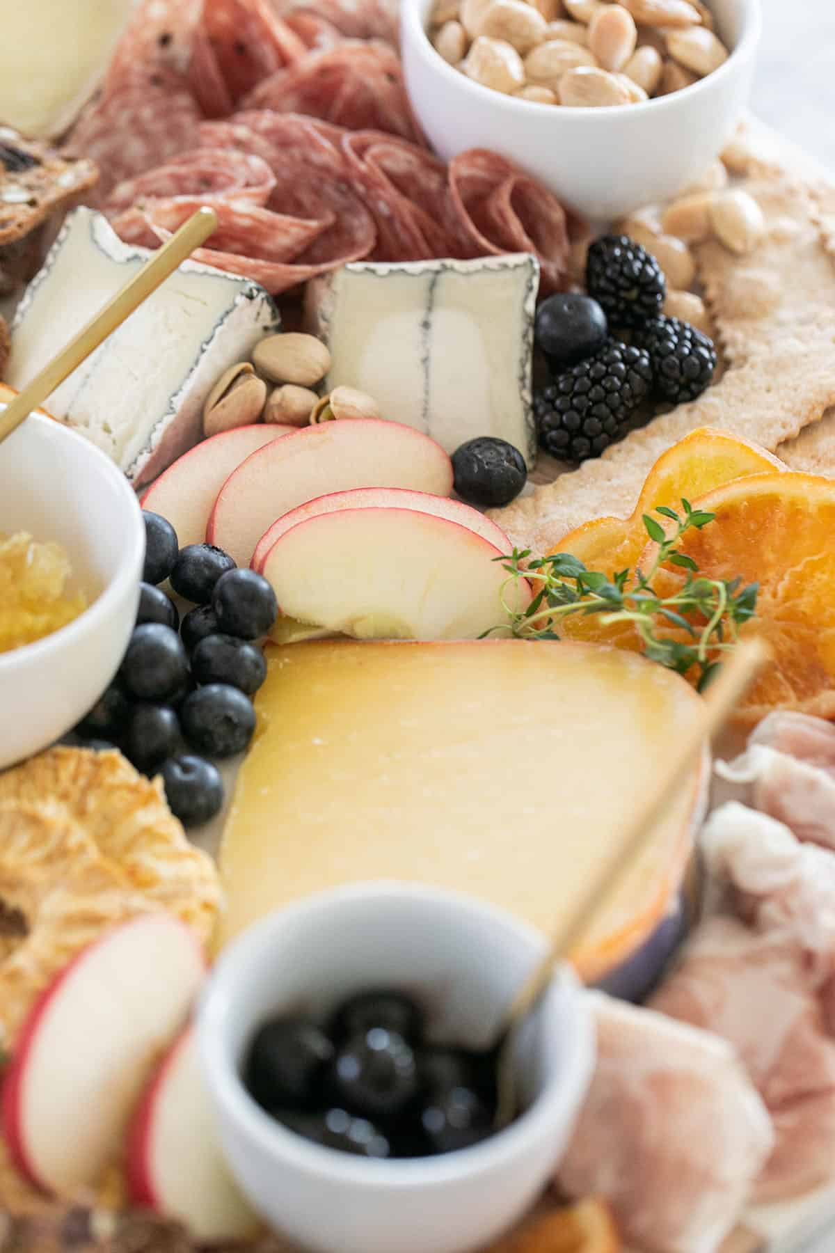 cheese platter with olives, fruit, meat and orange slices