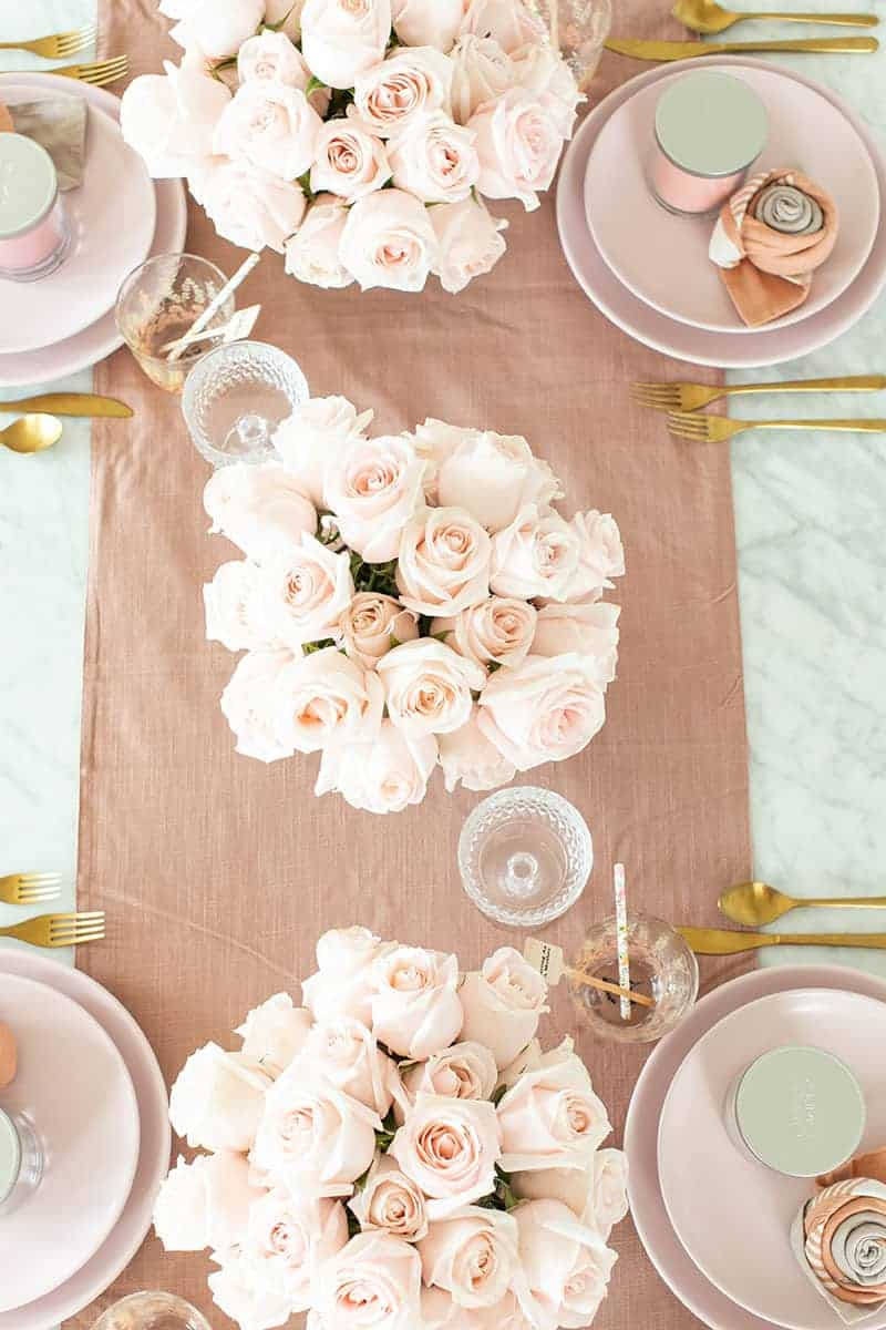 A pink table setting with roses and a pink table runner with pink dishes and gold flatware.