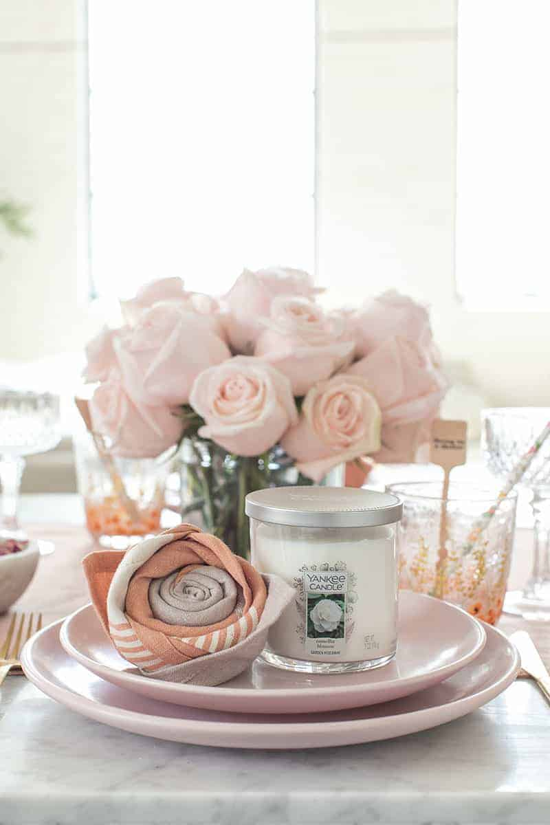 Table setting with a Yankee candle and rose napkin fold with pink flowers.