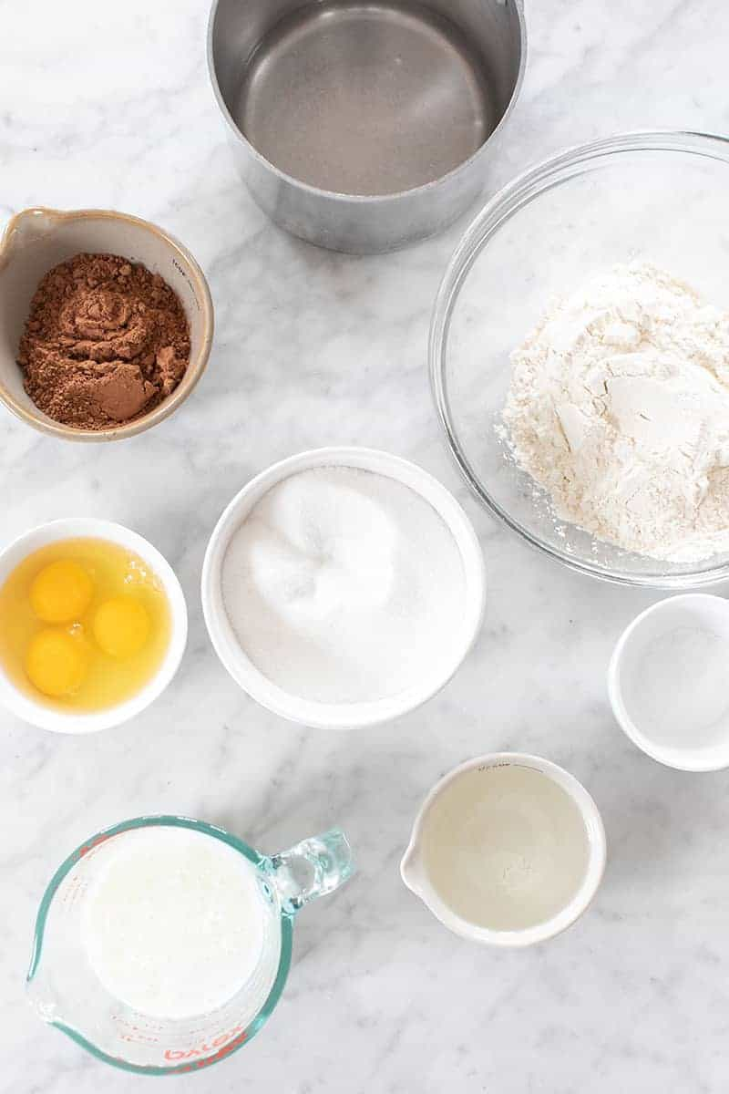 Sugar, flour, salt, eggs, cocoa powder and oil in bowls on a marble table.