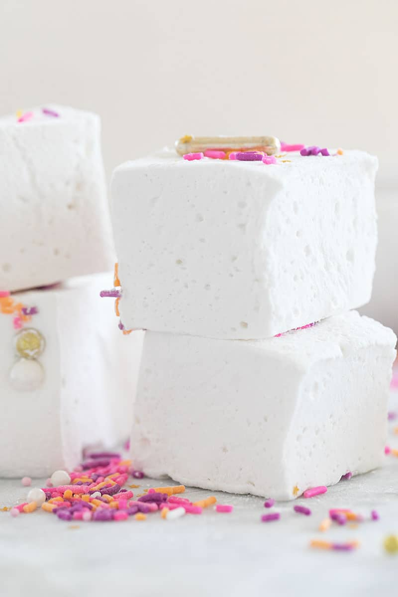 Four white fluffy marshmallows with sprinkles stacked on top of each other.