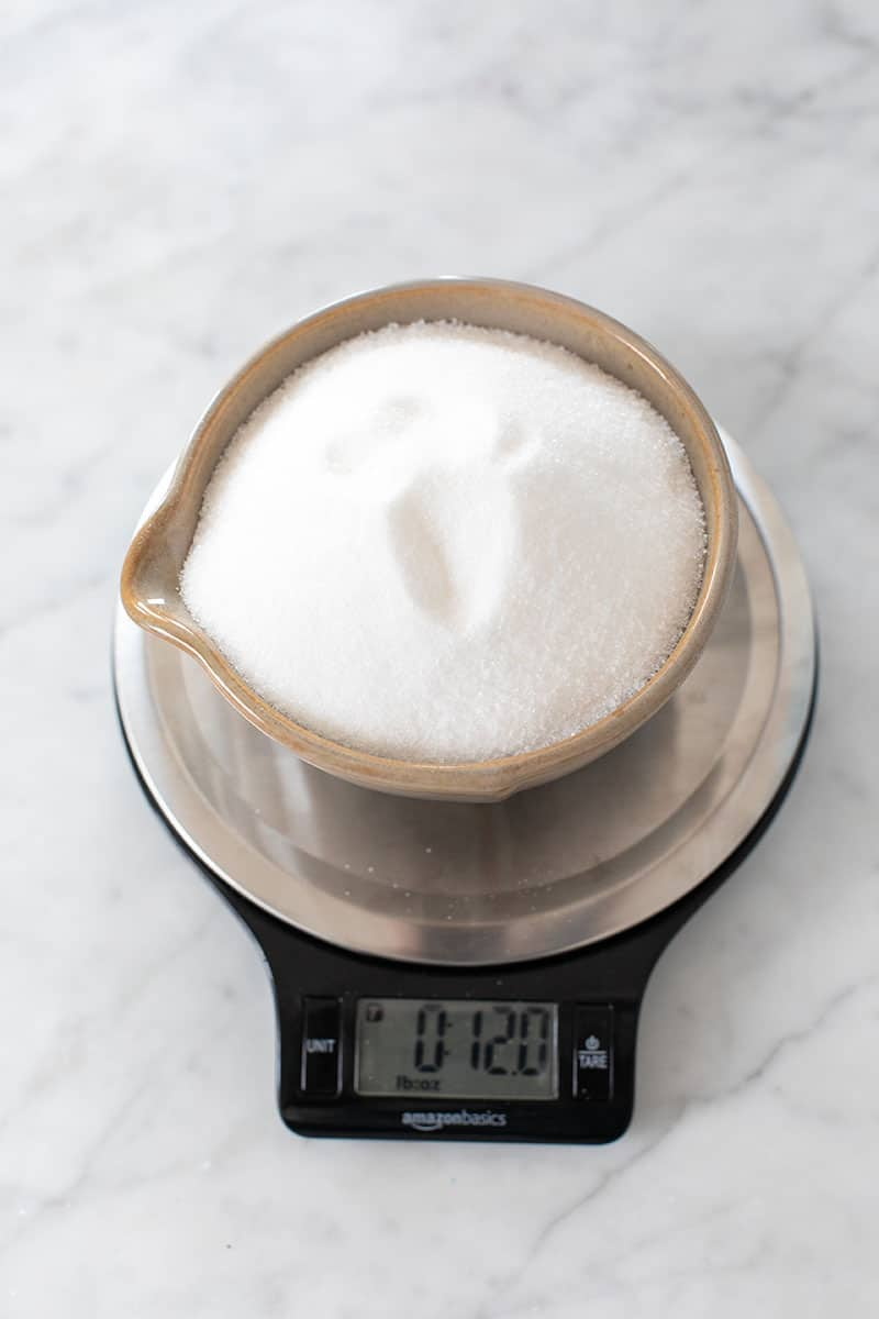 Cup of sugar on a kitchen scale.