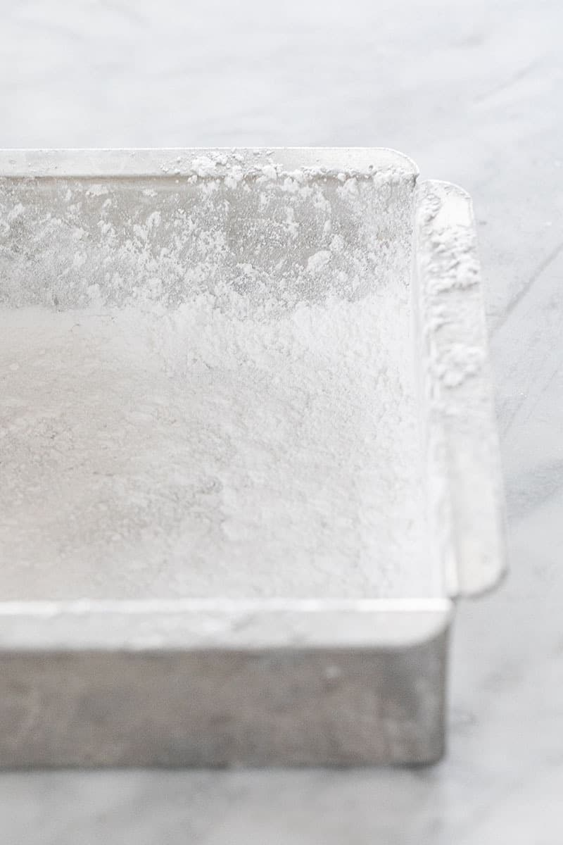 Preparing a baking dish with thick powdered sugar for marshmallows.