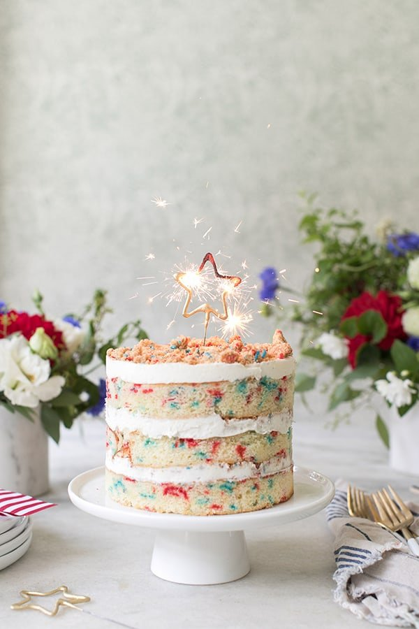 4th of July, red white and blue cake with a star sparkler lit and flowers.