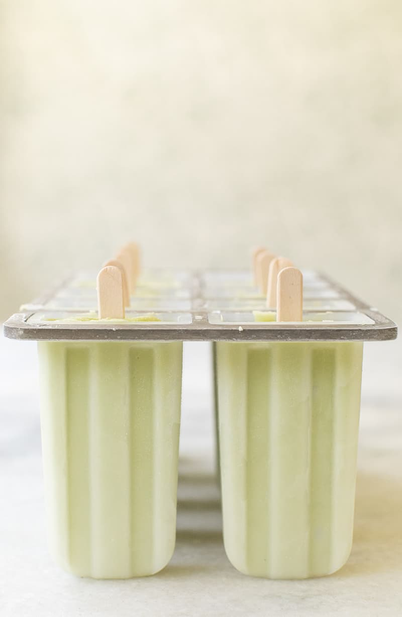 Green homemade popsicles in a popsicle mold.