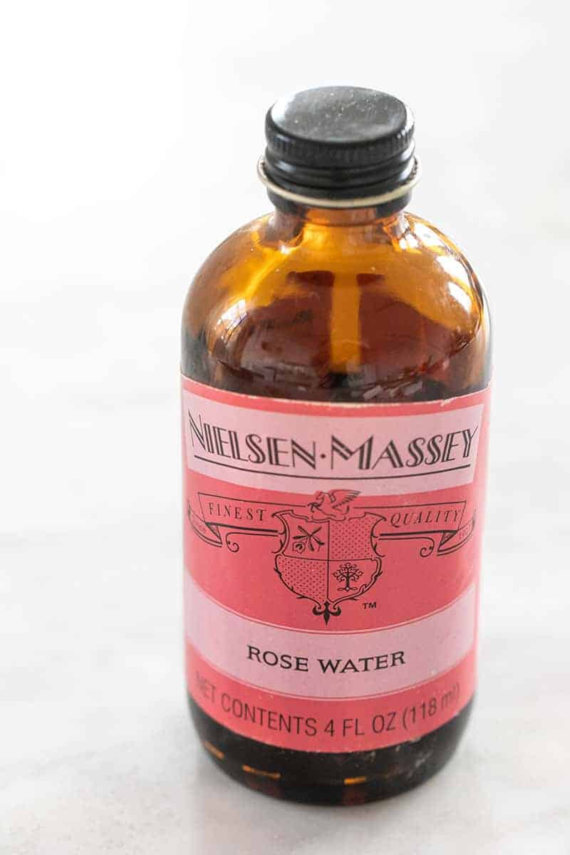 Rose water extract in a brown jar with a pink label.