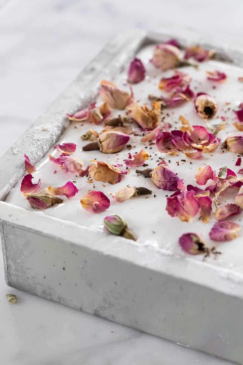 homemade marshmallows in a 6 x6 baking pan with rose petals over the top.