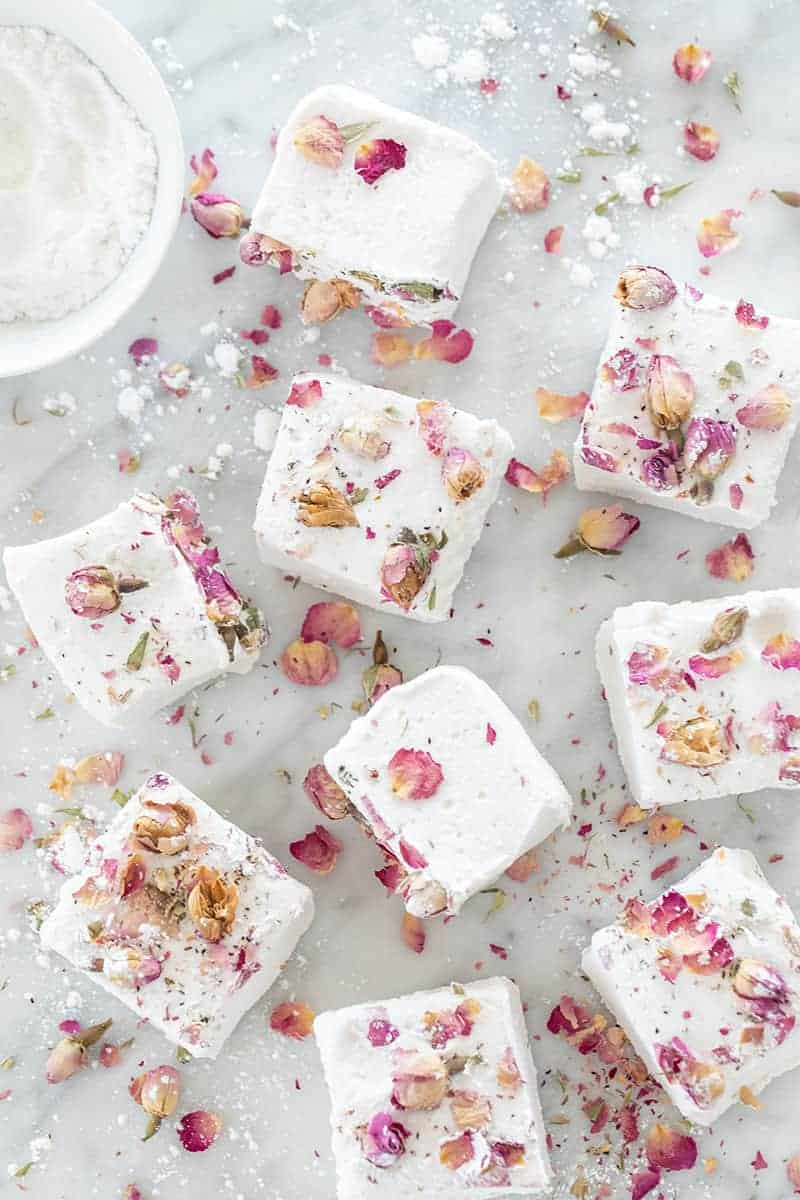 Giant, white fluffy homemade marshmallows with dried edible rose petals over them.