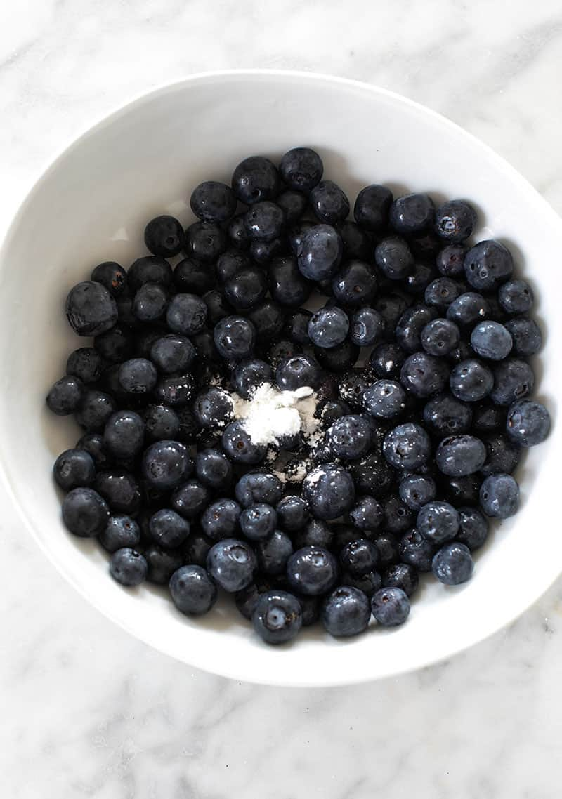 Blueberries with cornstarch in a white bowl.