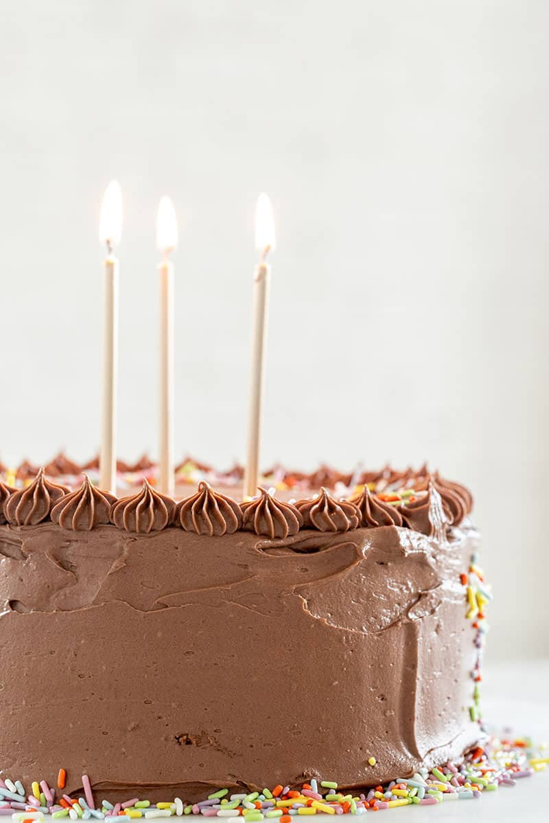 Birthday cake with candles and chocolate frosting with gold candles.