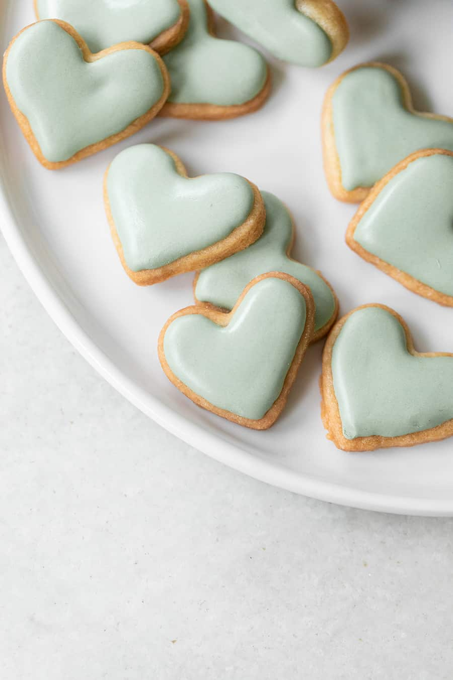Small heart shaped cookies with green royal icing.