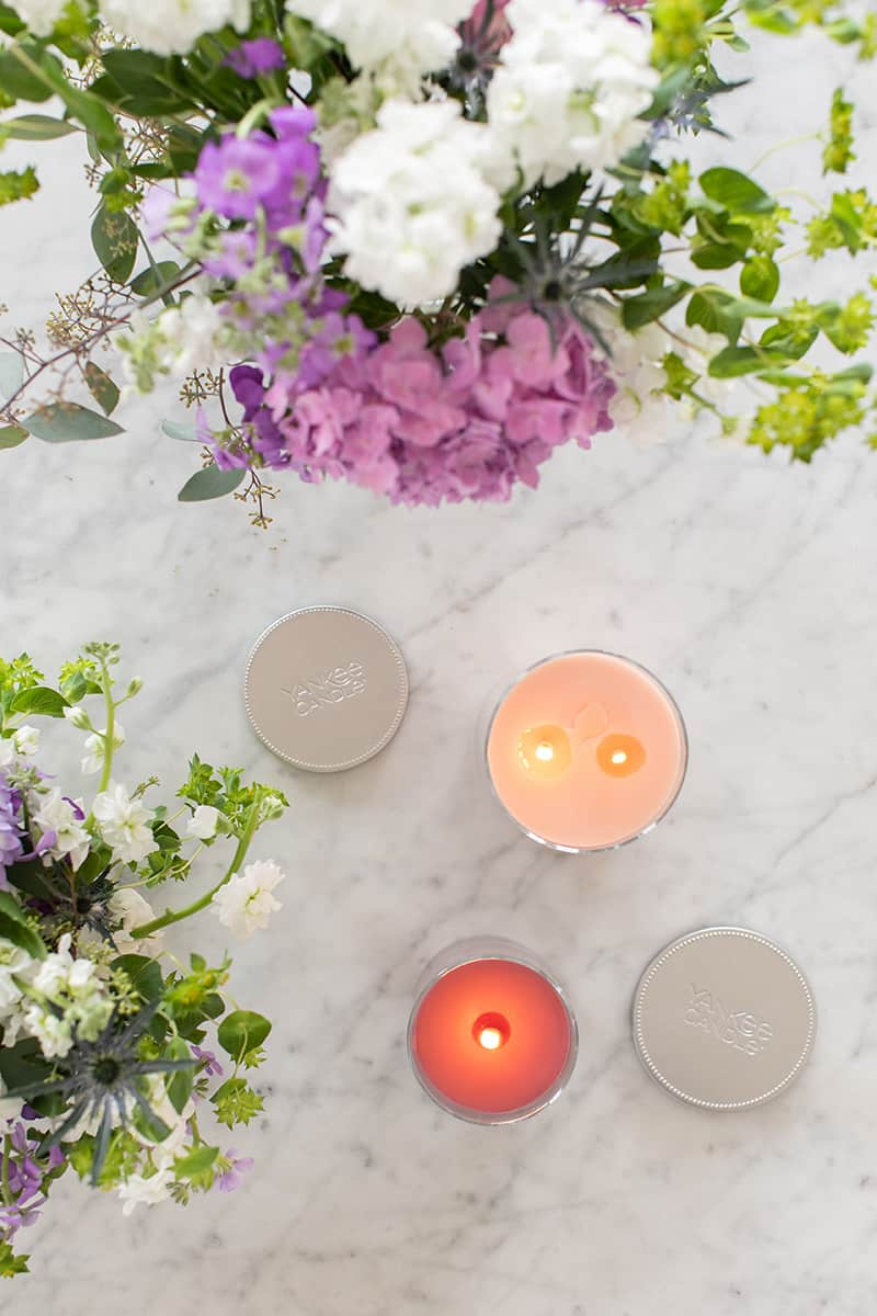 Flowers and candles on a marble table.