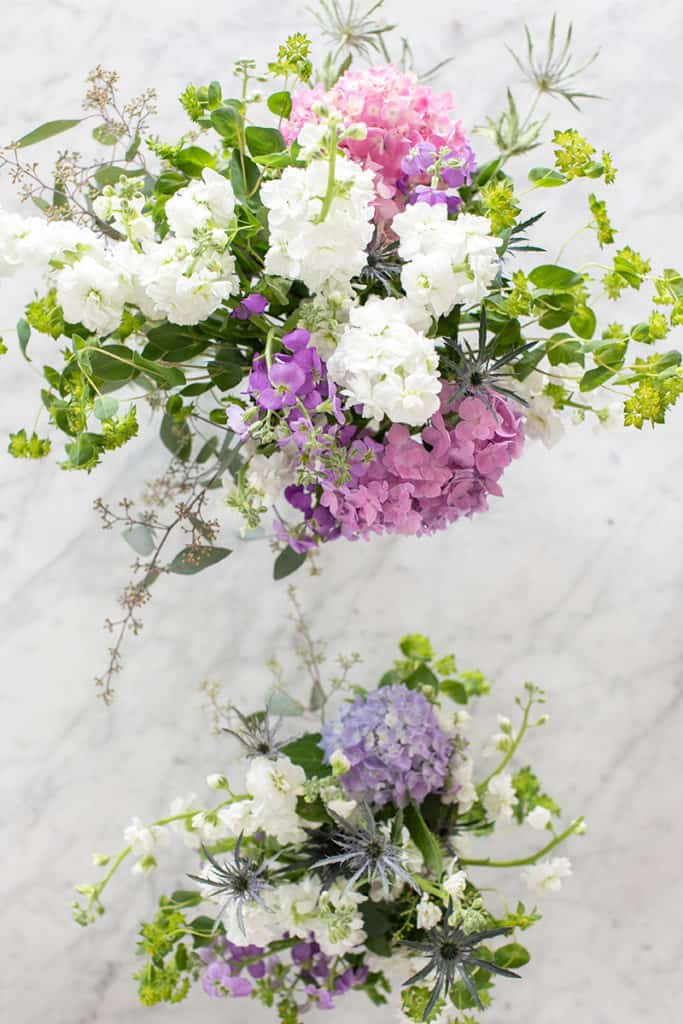 Purple and white flower arrangements  on a table.
