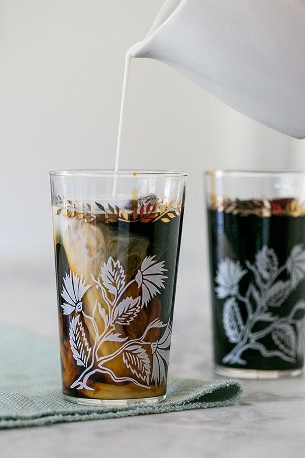 Pouring cream into cold brew coffee