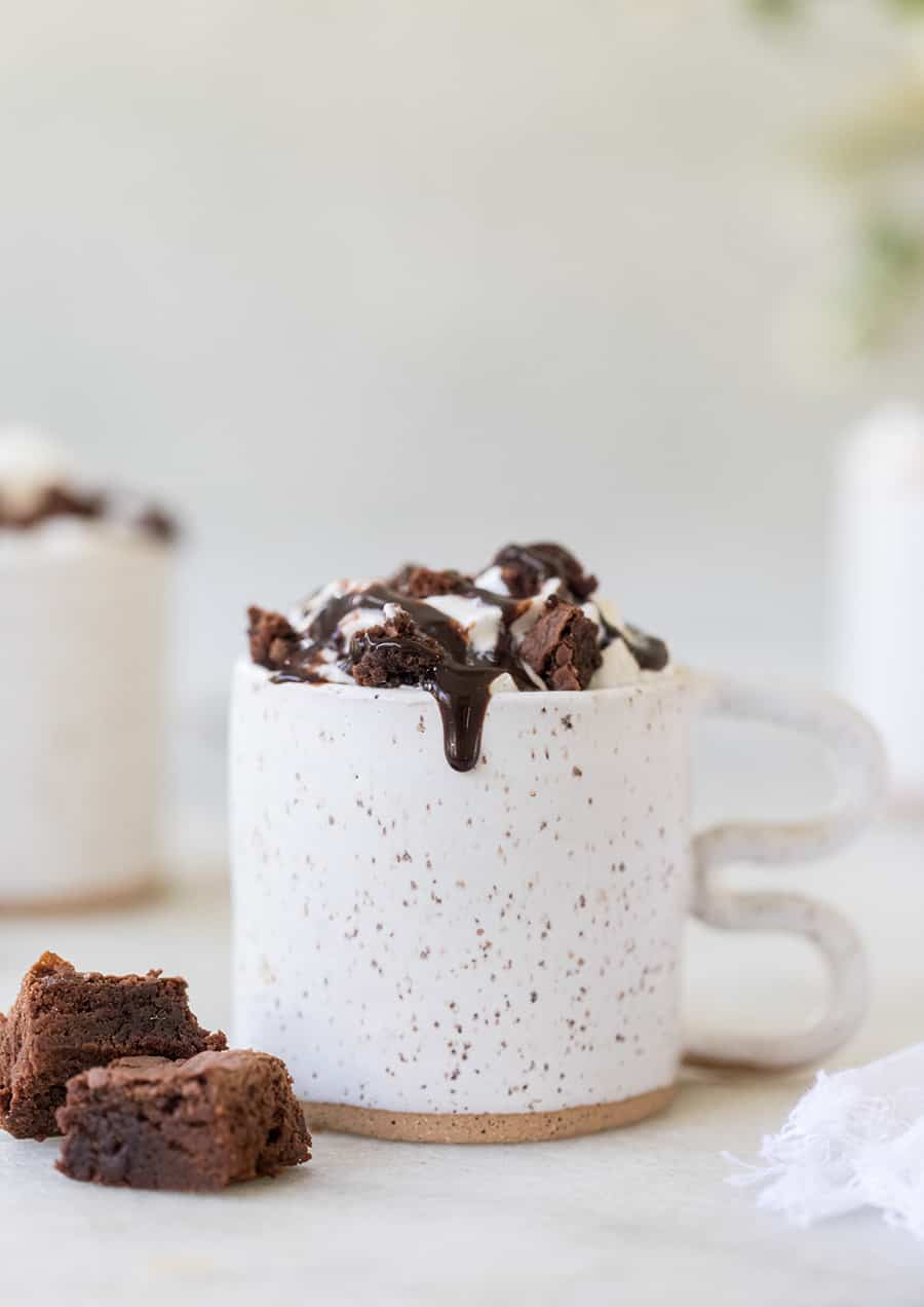 Coffee in a white ceramic cup with whipped cream, brownies and fudge.