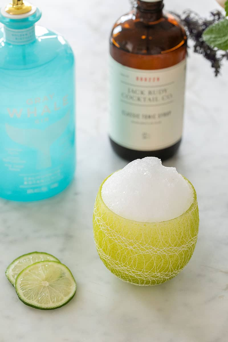 Gin and tonic snow cone in a green cup.