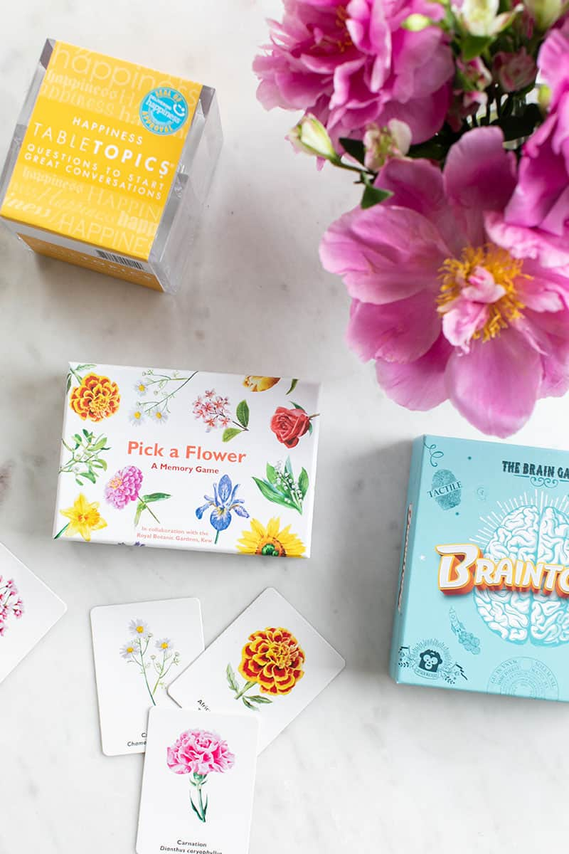 Games on a marble table with pink flowers.