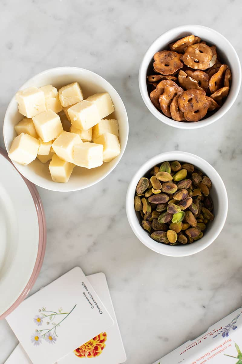 Cheese, pretzels and pistachios in small white bowls.