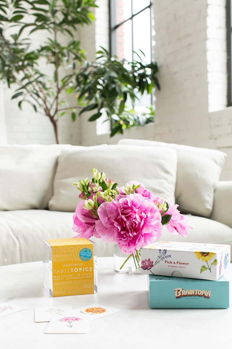 White couch with a family game night with pink flowers, ice cream cake and family games