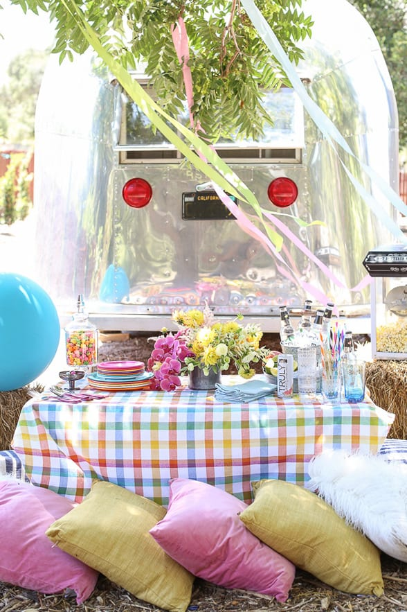 A colorful carnival birthday party with streamers, pink and yellow pillows, Airstream.