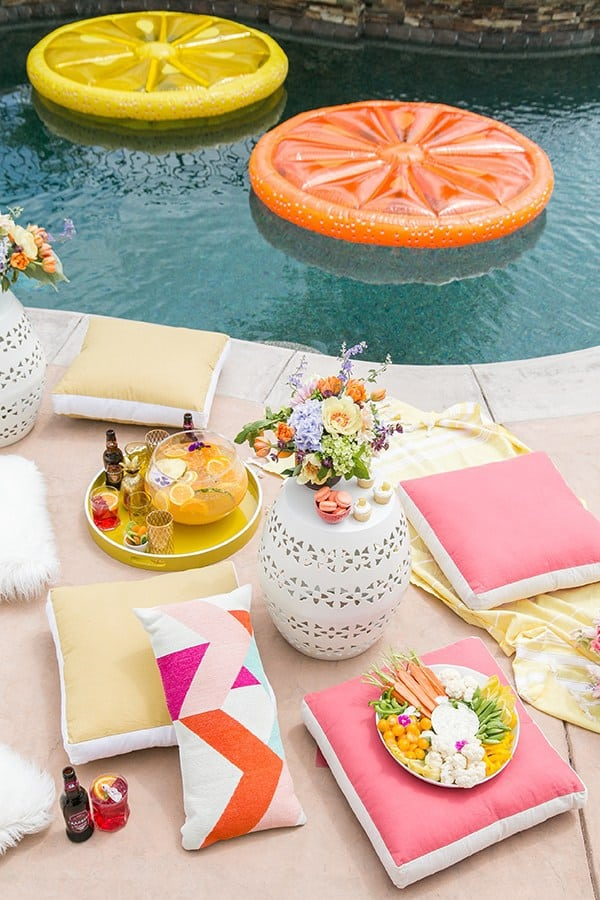 Pool party with citrus floats, pink and yellow cushions and flowers.