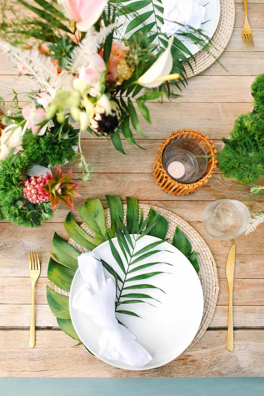 Tropical birthday party with white plates and ferns