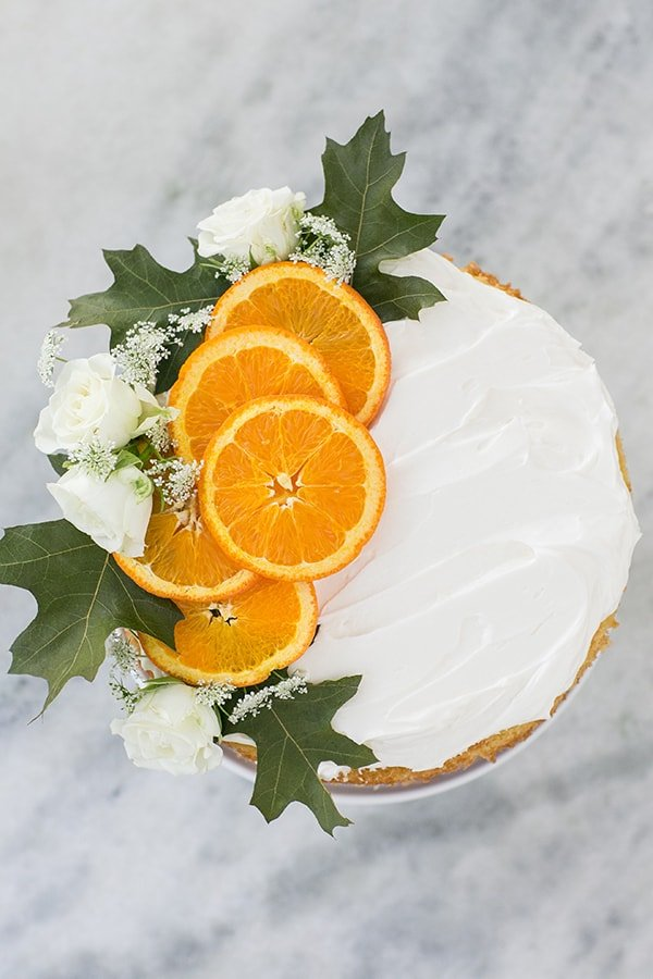 Orange rum cake with sliced oranges and flowers.