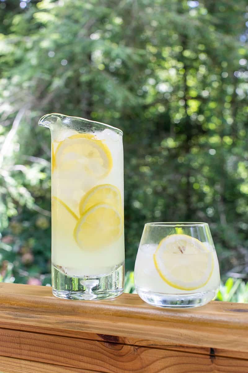 Pitcher of lemonade with a glass of lemonade.
