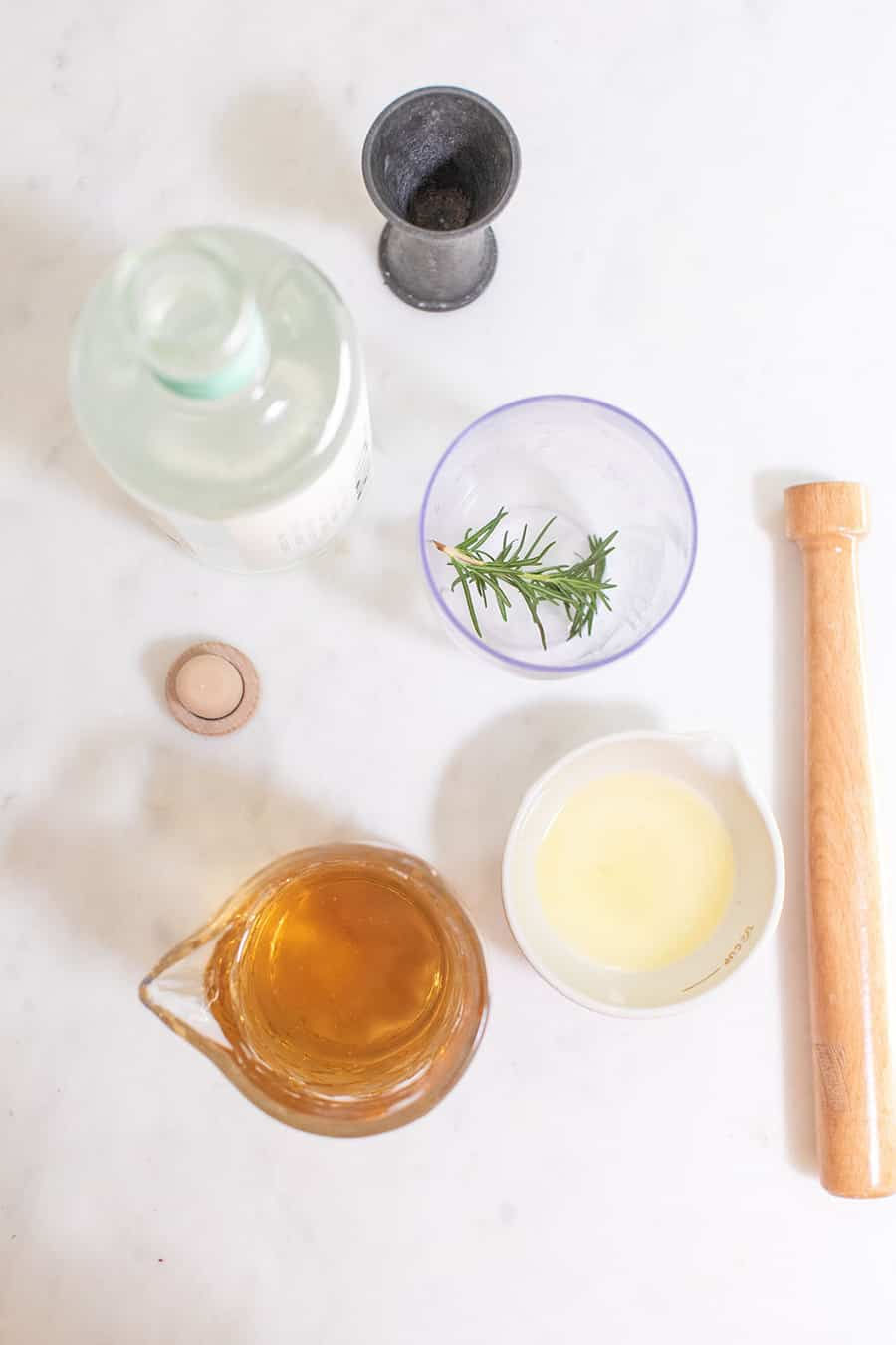 Ingredients to make a mocktail with lemon juice, rosemary, muddler.