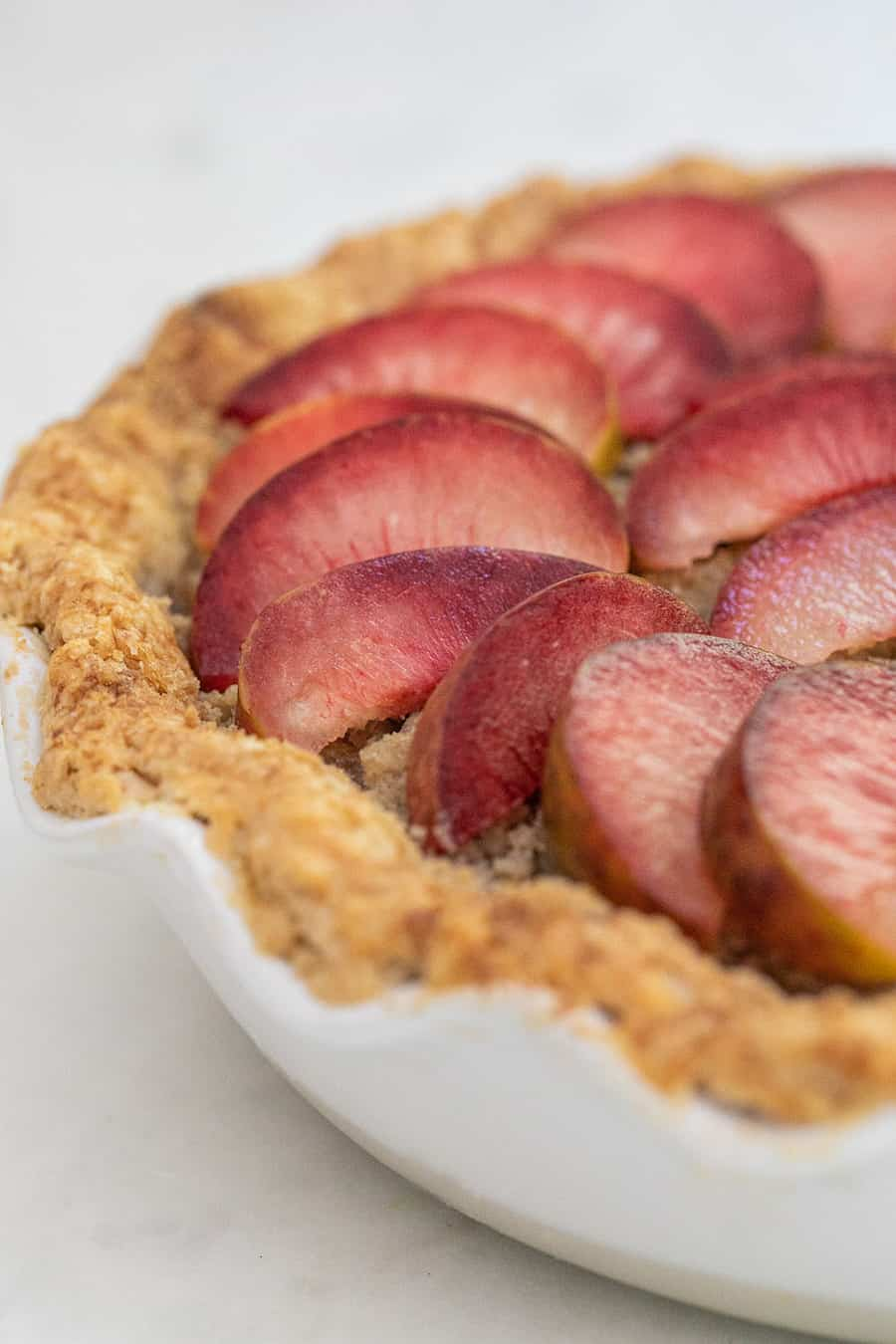 Aprium and plumcot pie with buttery pie crust and sliced plumcots.