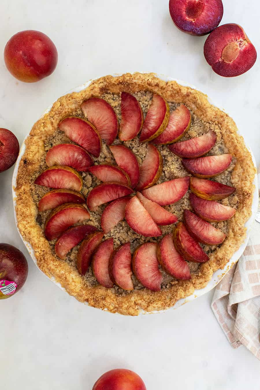Whole pie with crumble top and slice plumcots