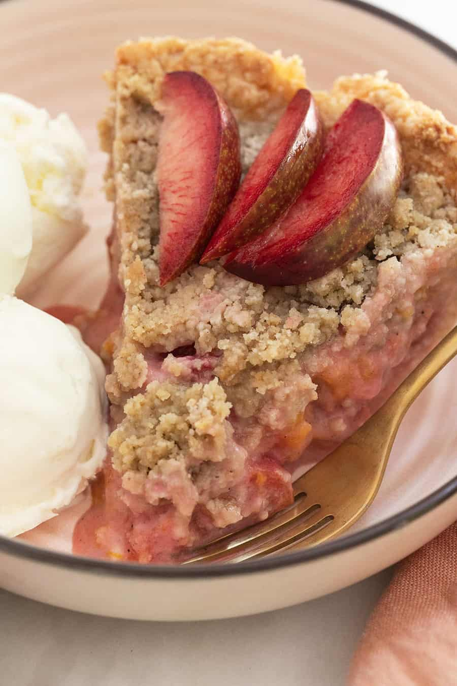 Plumcot and aprium pie with crumble top and sliced plumcots.